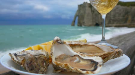 bivalve : Glass of white wine and a plate of oysters with lemon against the background of ocean waves