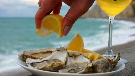 shellfish dishes : Hand squeezes lemon juice on fresh oysters against the background of ocean waves on the quay Etretat, Normandy