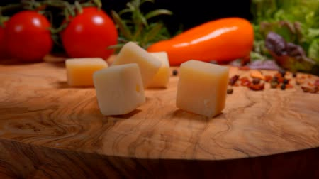 cheese types : Cubes of Parmesan cheese fall to the wooden surface of the table on the background of greenery and vegetables Stock Footage