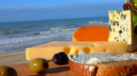 normandiya : Knife spreads soft cheese on bread on a wooden board in front of the Surf of the Atlantic Ocean Stok Video