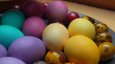 empilhamento : Womans hand laid red and green colored quail egg it to festive painted easter eggs on a gray plate