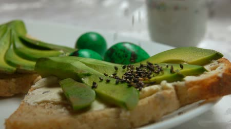 fürj : Black sesame falls on sandwich with avocado on a background of green Easter quail eggs. Easter breakfast