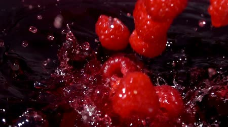 malina : Ripe red raspberries fall into juice with beautiful splashes in slow motion Dostupné videozáznamy