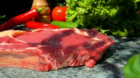 peppercorn : Veal steak falls on a green marble table. Still life of meat, herbs, spices and vegetables Stock Footage
