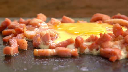 心のこもった : Camera movement along an egg with chopped bacon, roasted on the hot surface of the grill