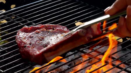 sürahi : Chef puts steak using metal tongs on the grill grate Stok Video