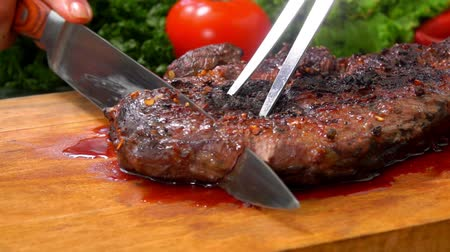 filet : Chef cuts the finished juicy beef steak on a wooden board with a large knife and fork Stock Footage