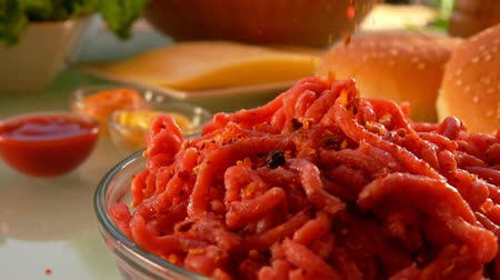 pastry ingredient : Spices fall on ground beef to make burgers. On the table prepared products for burgers Stock Footage