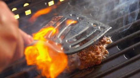 прессованный : Tasty beef burger flipping on the grill. Burger is pressed by kitchen spatula to the grill Стоковые видеозаписи