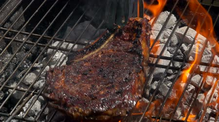 filet : Cook turns steak with metal tongs on a grill grate over an open fire.