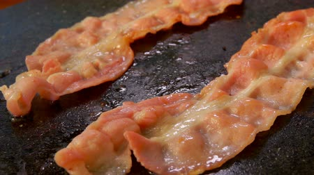 gevrek : Closeup of a two bacon strips hissing and frying on the hot stone surface. Movement of the chamber along several pieces of bacon