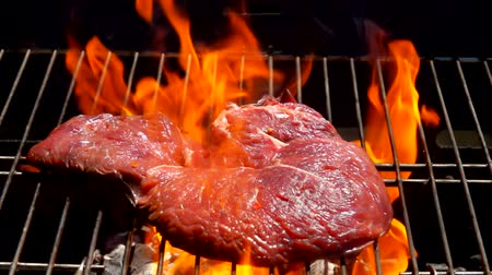 borjúhús : Cook lays the steak with a metal fork on the grill grate over an open fire Stock mozgókép