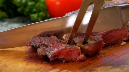 hátszín : Mistress cuts the finished juicy beef steak on a wooden board with a large knife and fork