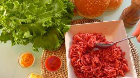 ground meat : Cook mixes ground beef with salt and spices to make hamburgers. On the table prepared products for burgers