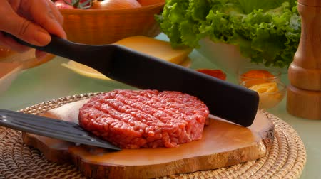 бекон : Cook raises cutlet for hamburgers with two spatula. On the table prepared products for burgers on sunny day in garden