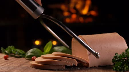 quebradiço : Special knife cuts a slice of foie gras in the background of a burning fireplace