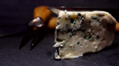 cheese slices : Knife cuts off a piece of blue-mold cheese on a black stone board close-up Stock Footage