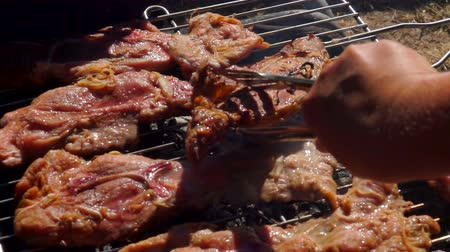 serving board : Chef turns lamb steak using metal tongs on the grill grate