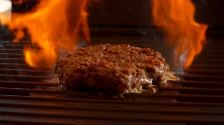 бекон : Tasty beef burger flipping on the grill. Burger is pressed by kitchen spatula to the grill Стоковые видеозаписи