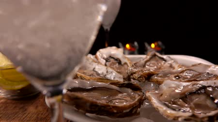 seafood dishes : Champagne is poured into a glass on the background of a served table with fresh oysters on ice and candles