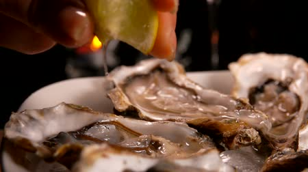 oysters : Hand squeezes lemon juice for fresh oysters in a plate