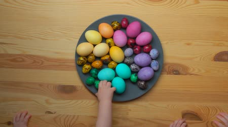 ilan : childrens hands taking multi-colored Easter eggs from a grey plate
