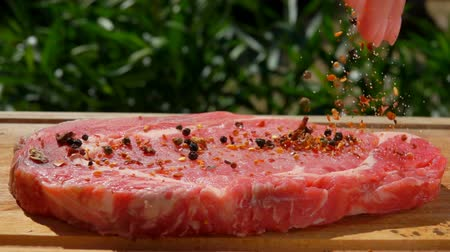 peppercorn : Mixture of spices falls on pork steak on a wooden board Stock Footage