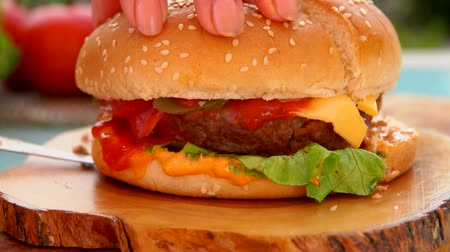 bacon burger : Knife cuts into half a delicious hamburger with cheese and tomatoes