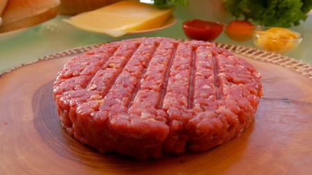 бекон : Raw beef burger lies on a wooden board on the table. Roundabout camera.