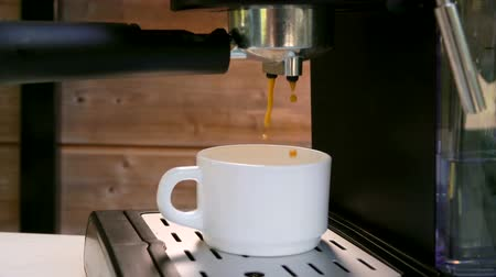 titular : Close-up of a drops of coffee dripping into a cup from a coffee machine