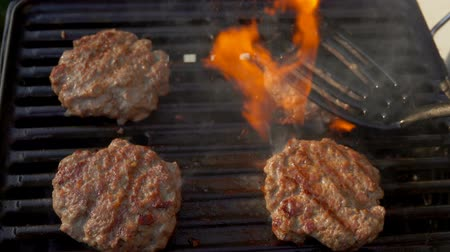 бекон : Tasty beef burgers flipping on the grill. Burgers is pressed by kitchen spatula to the grill Стоковые видеозаписи