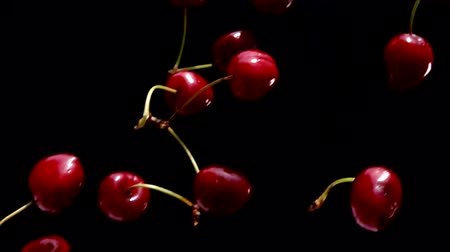 ягода : Rpe cherries fly on a black background closeup in slow motion