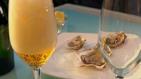 měkkýš : Champagne is poured into a glass on the background of a plate with oysters on ice.