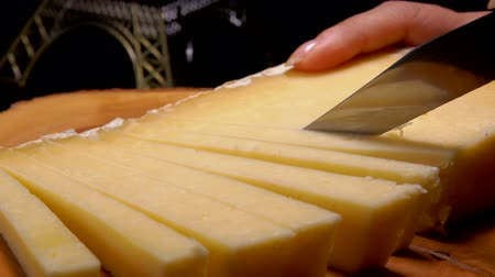 moldy : Knife cuts strips of hard cheese on a wooden board against the background of the Eiffel Tower model