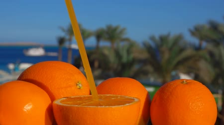 밀짚 : Large ripe juicy orange with a straw against the background of the sunny sea landscape