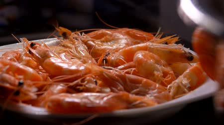 krewetki : Cooked shrimps fall into a white plate on the table.