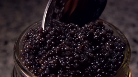 kaviár : Spoon takes black caviar from a glass jar close-up