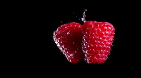çiğ gıda : Two berries of ripe raspberry are hitting each other on a black background