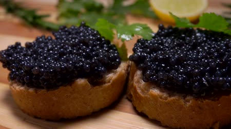 икра : Black caviar on white bread slices lies on a bamboo board