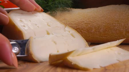 moldy : Knife cuts off a piece of soft sheeps cheese from whole milk for breakfast on a wooden board Stock Footage