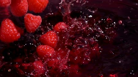 meyve suyu : Red juicyraspberries fall into juice with beautiful splashes in slow motion
