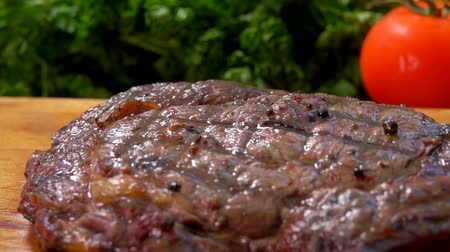 filet : Panorama of the finished juicy steak, lying on a wooden cutting board Stock Footage