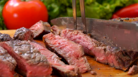 sürahi : Chef cuts the ready-made juicy steak on a wooden board with a large knife and fork