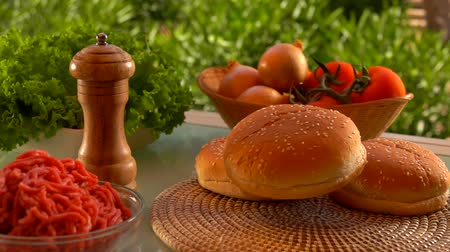 бекон : Bun for hamburger falls on the table. On the table prepared products for burgers Стоковые видеозаписи