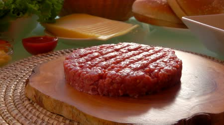 molho de tomate : Cutlet for a hamburger lies on a wooden cutting board. On the table are preparing foods for hamburgers. Stock Footage