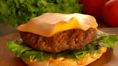 dilimleri : Piece of cheese falls on a hamburger. On the table prepared products for burgers Stok Video