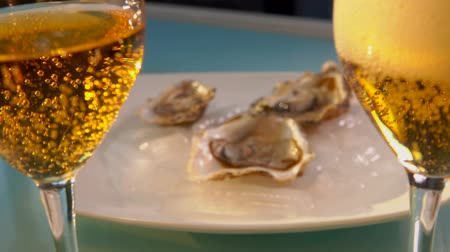 ostrica : On the table stands a sparkling wine against the background of a plate of oysters on ice and bowls of lemon