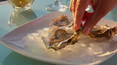 istiridye : Female hand puts open oysters on a plate with ice. Bowl of lemonsbowl of lemons