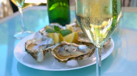 oysters : Fresh tasty oysters lie in a plate with ice on a table with wine outdoors. Stock Footage