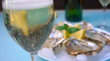 oysters : Bubbles of champagne rise to the top in a wineglass on the background of a plate with oysters on the ice and lemon on a picnic table.